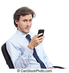 Young businessman sitting on a chair using a smart phone...