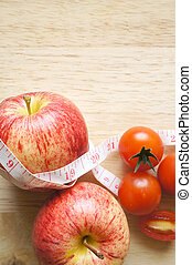 Diet concept. Apple with measuring tape an tomatoes