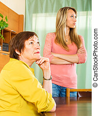 Upset mature mother against adult daughter after conflict
