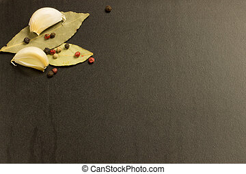 bay leaf with garlic and pepper on a black background