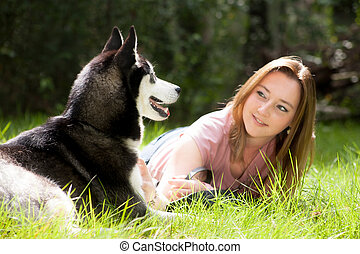 Woman and her dog - Young woman and her husky in the forest