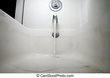 Dirty Bathtub with Water - A dirty bathtub being filled with...
