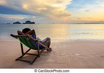Man on sun loungers stand at sunset beach