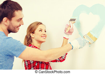smiling couple painting small heart on wall - repair,...