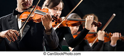 Violin orchestra performing on stage on dark background.