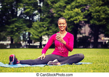 smiling african american woman with smartphone - fitness,...