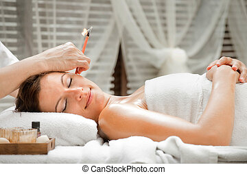 Ear Candling in Spa - Ear candling being carried out on an...