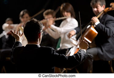 Conductor directing symphony orchestra with performers on...
