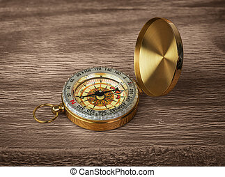 Retro brass compass on a wooden background
