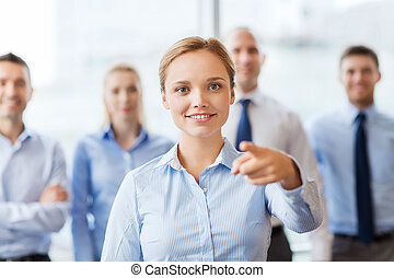 smiling businesswoman pointing finger on you - business,...