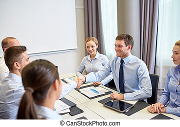 group of smiling business people meeting in office -...