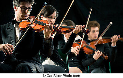 Violin orchestra performing on stage on dark background
