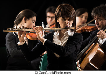 Symphony orchestra performance: flutist close-up -...