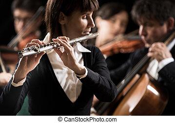 Classical music concert: flutist close-up - Female flutist...