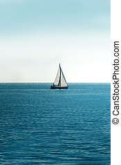 White sailboat on the ocean at midday