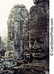 Gigantic face statues on the Bayon Temple in the walled city/ruin of Angkor Thom at the UNESCO World Heritage archaeological ruins of Angkor Wat- Siem Reap, Cambodia