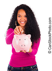 Young african american woman putting coin in piggy bank...