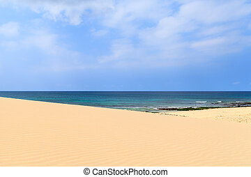 Sand dunes near to the ocean with cloudy blue sky, Boavista,...