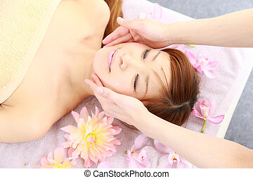 face massage - studio shot of young Japanese woman getting a...