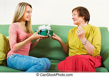 Daughter congratulating happy mature mother