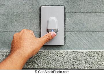 Hand pressing doorbell