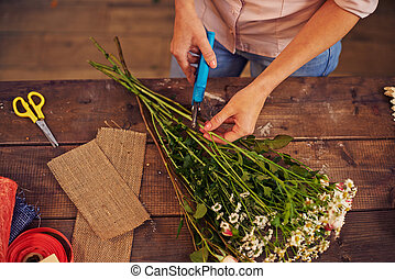 Shortening floral stems - Female florist cutting floral...