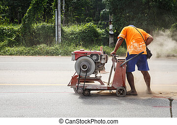 Cutting asphalt road for repair by hydraulic driven angle...