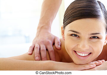 Relaxing massage - Smiling female looking at camera during...
