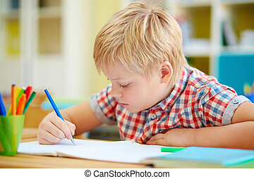 Lesson of writing - Little schoolboy writing in copybook at...