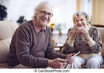 Seniors at home - Smiling senior man with touchpad looking...