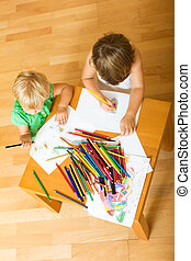 Siblings playing with pencils - Two year children playing...