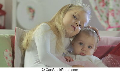 Older sister hugs and strokes head of the younger cute baby