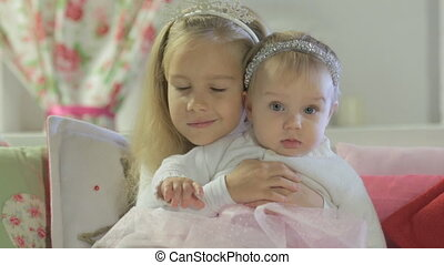 Beautiful little girl sitting with her little sister on the...