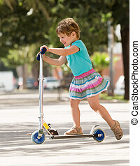 4 years old girl staying with scooter
