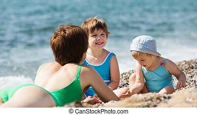 mother with happy children at sand beach