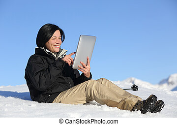 Happy hiker woman browsing a tablet on the snow - Happy...