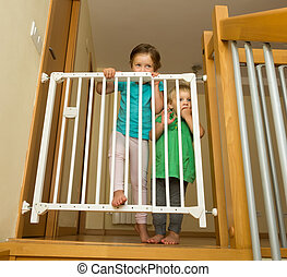 Two girls approaching safety gate - Two little girls...