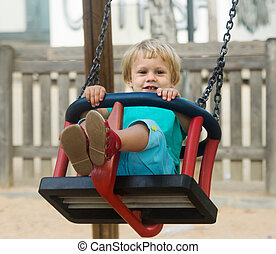 2 years child on swing against urban landscape
