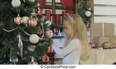 Cute little girl decorates the Christmas tree in festive...