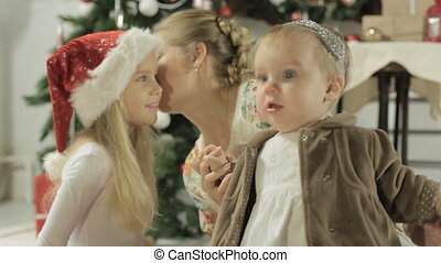 Family sitting near decorated Christmas tree, young mother...
