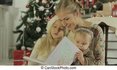 Beautiful young mother sitting with two adorable little girls and reading book
