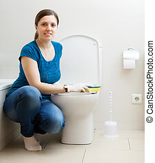 Smiling girl cleaning toilet bowl - Smiling girl in blue...