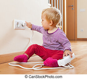 Toddler playing with extension cord and electric outlet at...