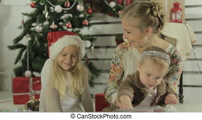 Beautiful mother reads fairy story to her little daughters...