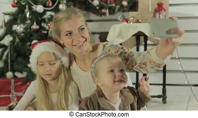 Charming mom with two lovely daughters makes the photo on phone