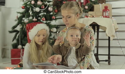 Happy mother with two cute daughters sitting by the Christmas tree and reading a book