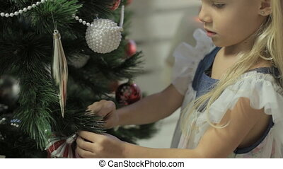 Little lovely girl in beautiful dress decorates Christmas...