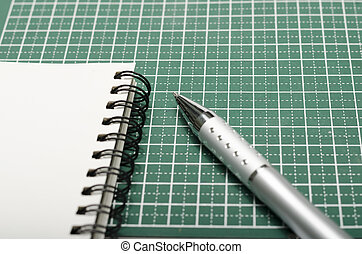 notebook and pen on cutting mat