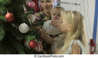Little cute girl in a beautiful dress with long blond hair decorates a Christmas tree