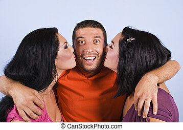 Happy man with two kissing women